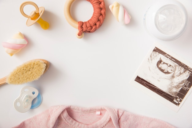 Pacifier; marshmallow; brush; toy; milk bottle; sonography picture and baby onesie on white background Free Photo