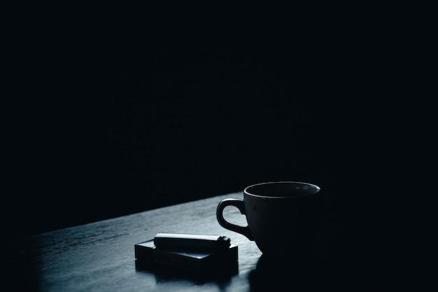 Un pacchetto di sigarette e un bicchiere di caffè Foto Gratuite