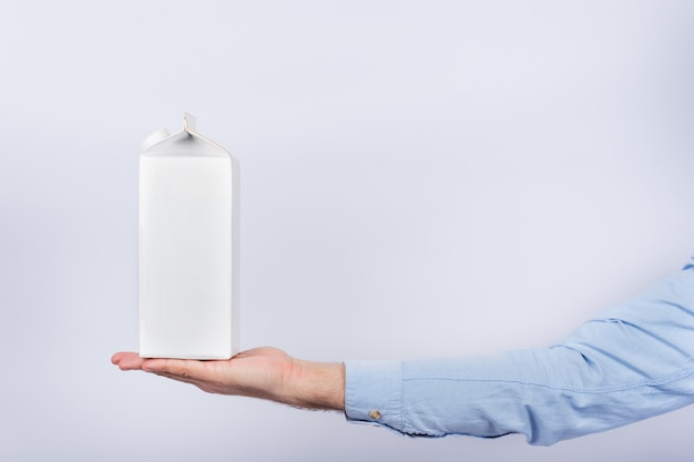 Pack of milk on male palm on white wall. copy space, mock up Premium Photo