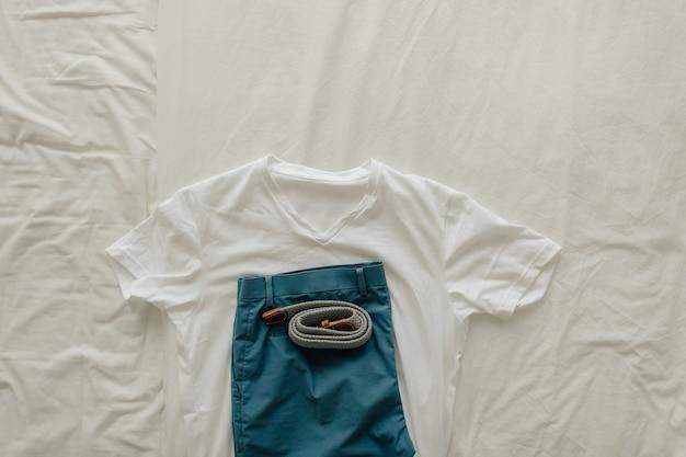흰색 티셔츠 파란색 짧고 옷을 입은 벨트가 달린 흰색 침대에 옷 팩. 프리미엄 사진