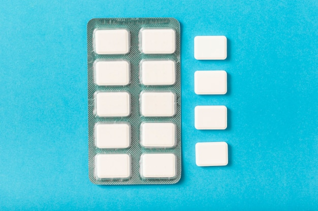 Pack of white chewing gum blister on blue background Free Photo