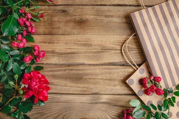 ハンドル水玉とストライプと木製の背景に自然な赤いバラの包装袋。 copyspace付きフラットレイアウト Premium写真