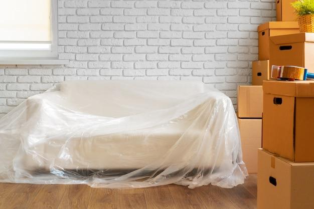 Упакованный диван и стопка картонных коробок в комнате Premium Фотографии