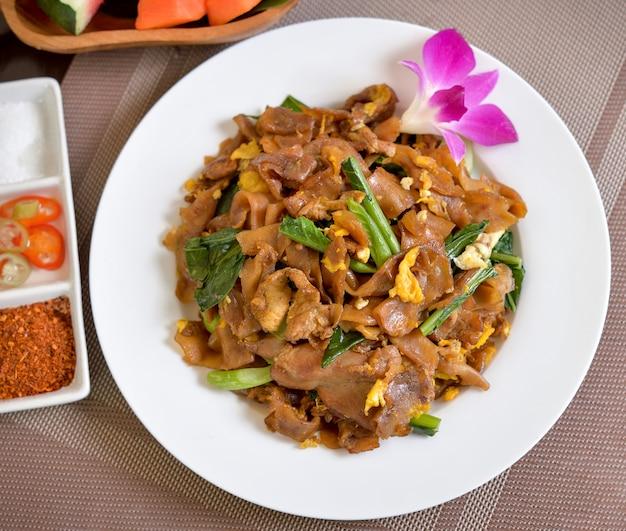 平らな麺と豚肉の濃い醤油炒め(タイ人はpad see ewと言います) Premium写真
