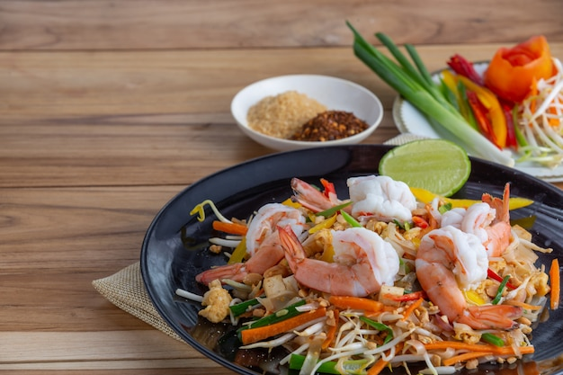 Pad thai, fresh shrimp in a black dish, placed on a wooden table. Free Photo