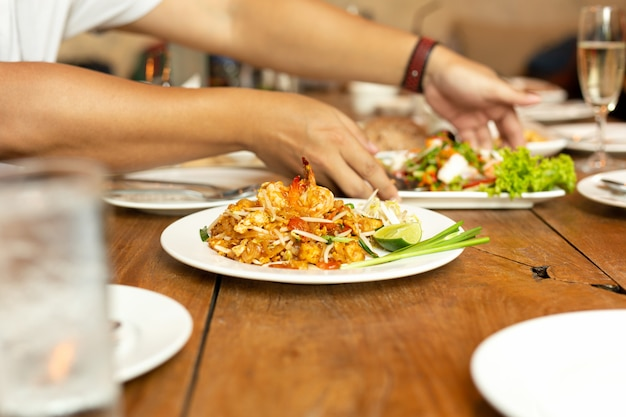 Pad thai noodles with shrimp on whit plate on wooden table in restaurant. Premium Photo