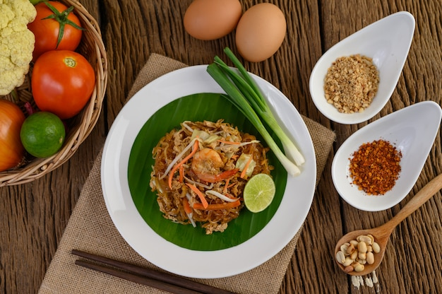 Padthai shrimp in a black bowl with eggs, spring onion, and seasoning on wooden table. Free Photo