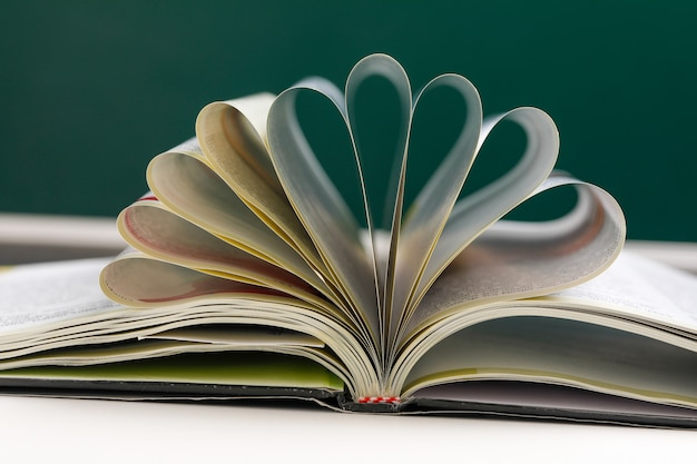 Pages of book curved into a heart shape. Premium Photo