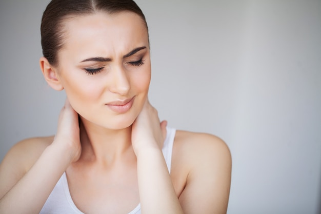 Pain. beautiful young woman feeling sick and has a pain in the neck Premium Photo