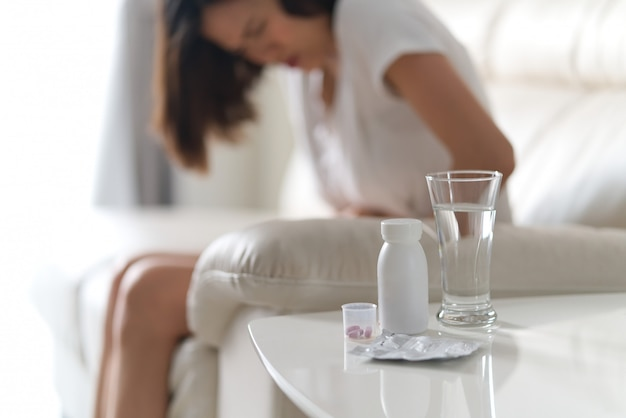 Painful sickness stomach ache woman sitting on the sofa at home. Premium Photo