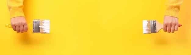 Paint brush in the hand of a girl on yellow Premium Photo