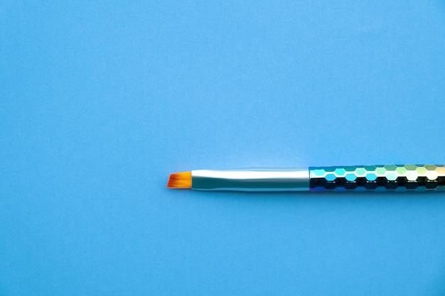 파란 종이 배경에 페인트 브러시입니다. 무료 사진