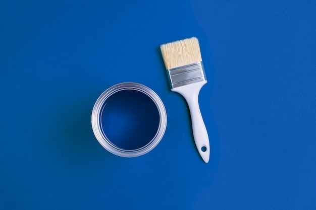 Paint brush with an open can of paint on trendy classic blue background. color of the year 2020. Premium Photo