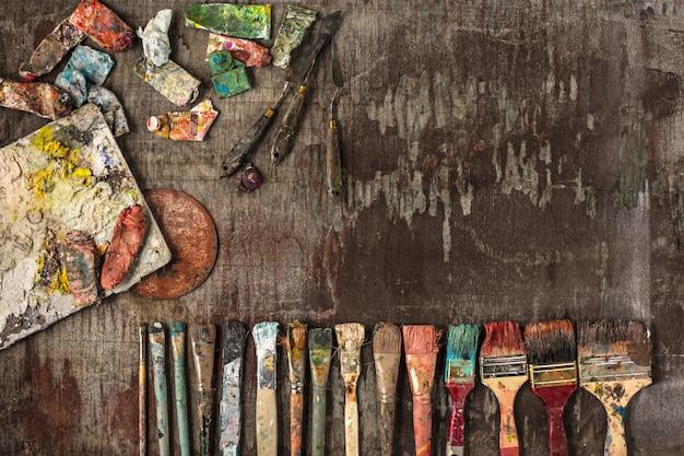 페인트 브러시 및 나무 테이블에 유성 페인트 튜브 무료 사진