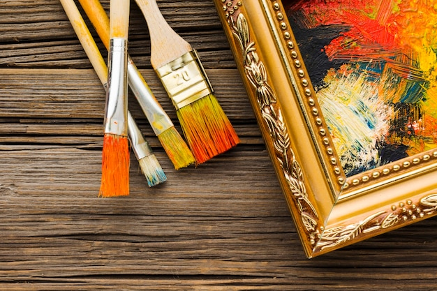 Paint brushes and painted canvas in frame Free Photo