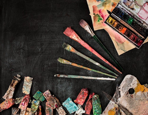 Paint brushes and tubes of oil paints on wood Free Photo