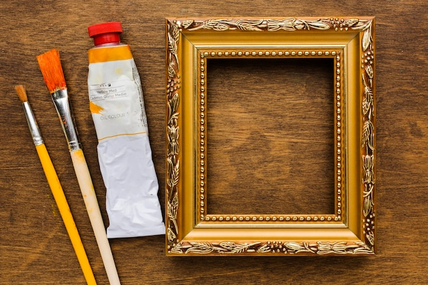 Paint and brushes with empty frame Free Photo