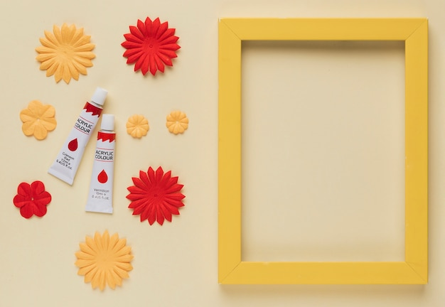 Paint tube; flower cutout and yellow wooden frame border on beige background Free Photo