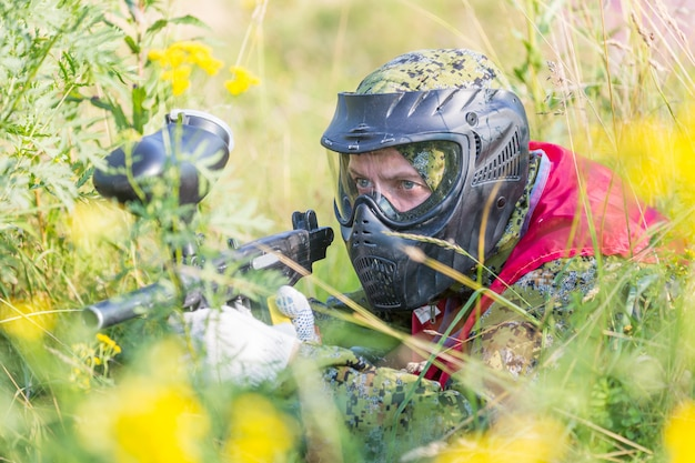 Paintball sport player in protective uniform and mask playing with gun outdoors and sneaking in grass. Premium Photo