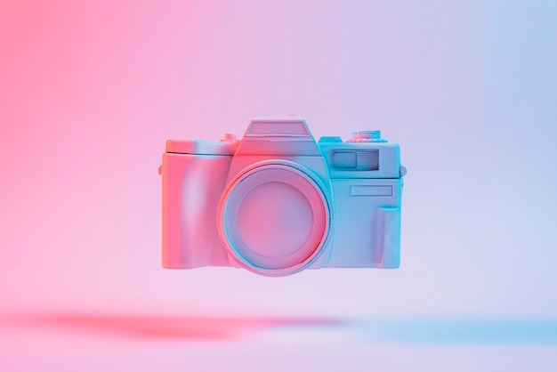 Painted camera floating with shadow against pink backdrop Premium Photo
