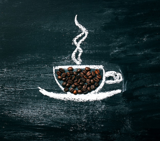 Painted cup of coffee with natural coffee beans on a chalkboard. Free Photo