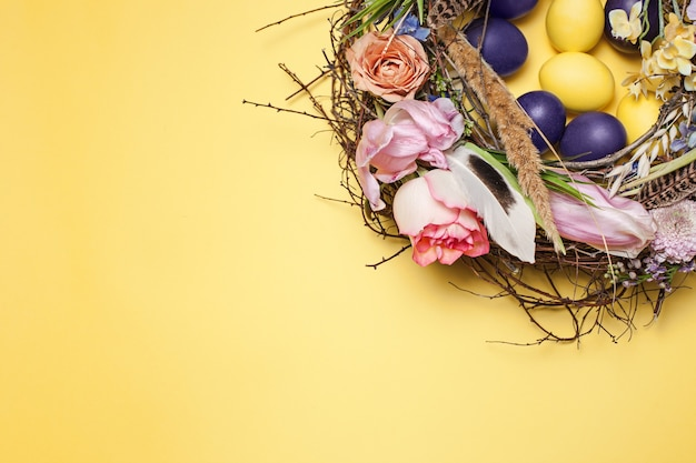 Painted easter eggs in nest on yellow table background. top view of easter decoration. happy easter concept. trendy colors Free Photo