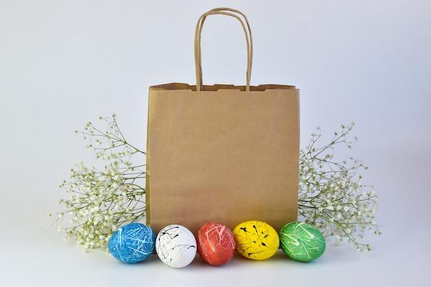 塗られた卵と花は紙袋の隣にあります。イースターの配達。スペースのコピー。広告ブランディング。 Premium写真