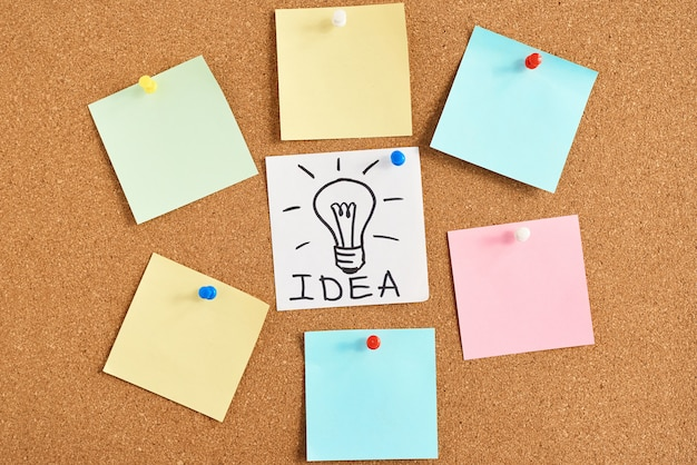 Painted light bulb with word idea and colored blank notes on a cork board Premium Photo