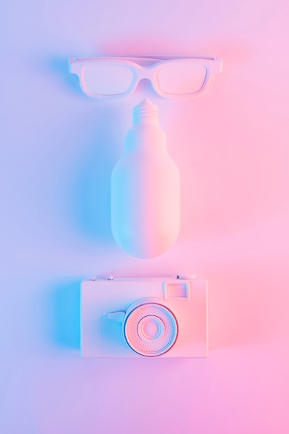 Painted sunglass; led light bulb and vintage camera against pink background Free Photo