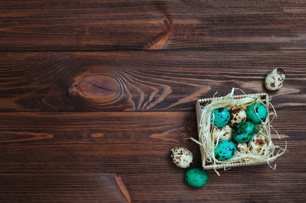 Painted turquoise quail eggs on wooden background Premium Photo