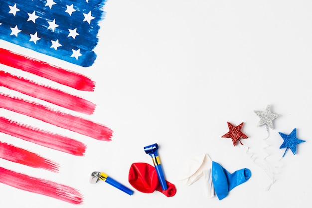 Painted united states american flag with party horn; balloons and star props on white background Free Photo