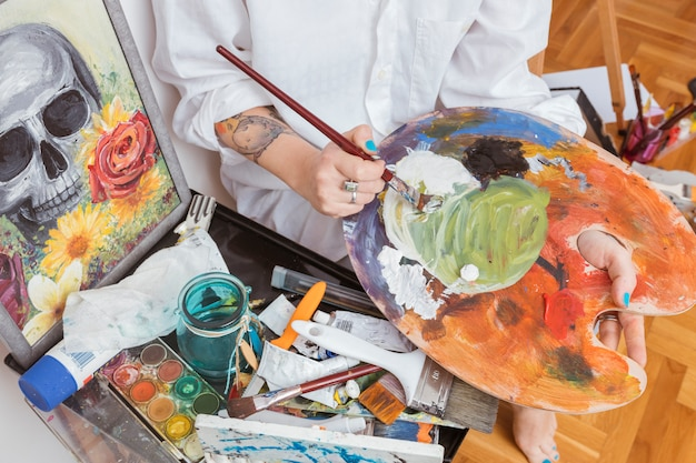 Painter dipping brush in dye on palette Free Photo