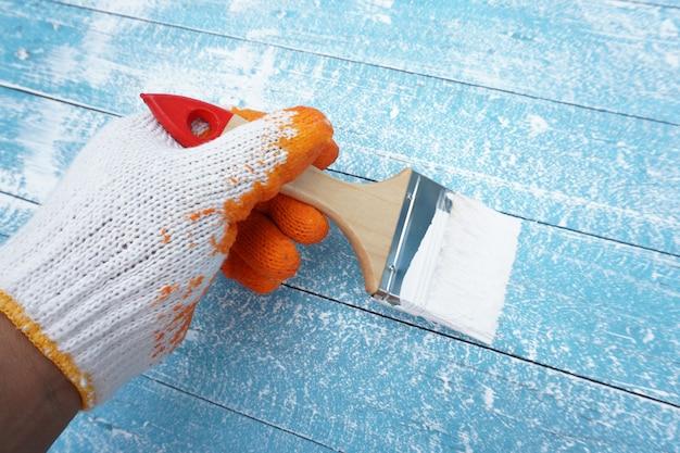 Painter hand holding brush paint the blue wood Premium Photo