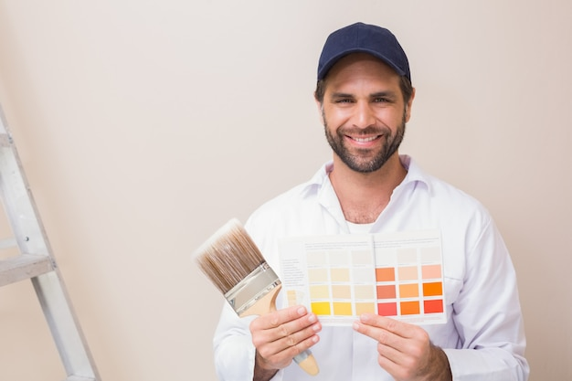 Painter holding a colour chart smiling at camera Premium Photo
