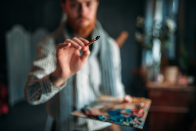 Painter with palette and brush in hand Premium Photo