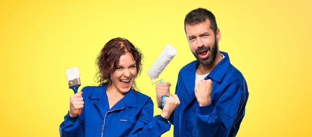 Painters celebrating a victory and happy for having won a prize on colorful background Premium Photo