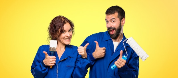 Painters giving a thumbs up gesture and smiling because has had success Premium Photo