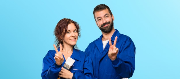 Painters happy and counting two with fingers on colorful background Premium Photo