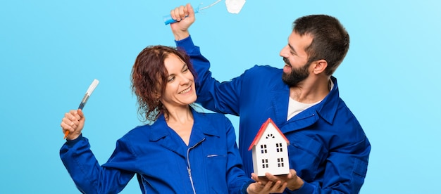 Painters holding a little house on colorful background Premium Photo