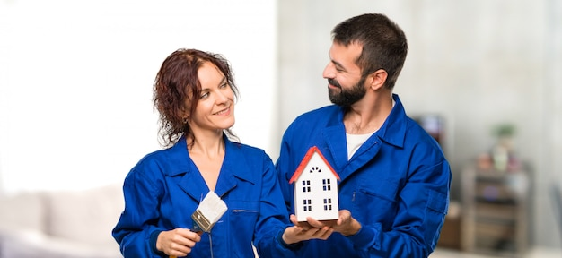 Painters holding a little house in house Premium Photo