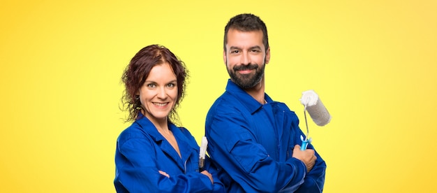 Painters keeping the arms crossed in lateral position while smiling on colorful background Premium Photo