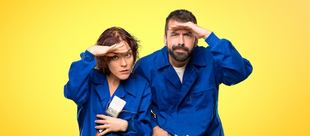 Painters looking far away with hand to look something on colorful background Premium Photo