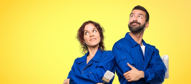 Painters looking up while smiling on colorful background Premium Photo