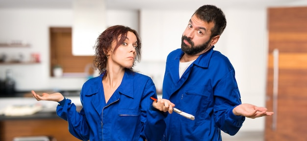 Painters making doubts gesture while lifting shoulders in house Premium Photo