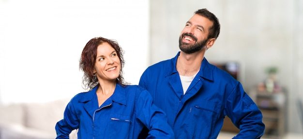 Painters posing with arms at hip and laughing in house Premium Photo