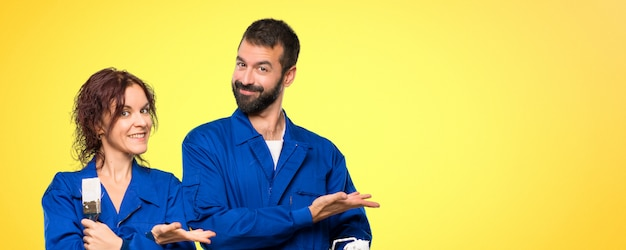 Painters presenting an idea while looking smiling towards on colorful background Premium Photo