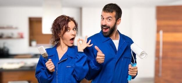 Художники, показывая знак ок и давая пальцем вверх жест другой рукой в доме Premium Фотографии
