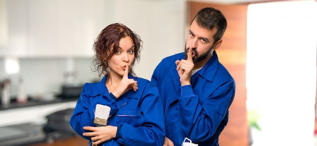 Painters showing a sign of closing mouth and silence gesture in house Premium Photo