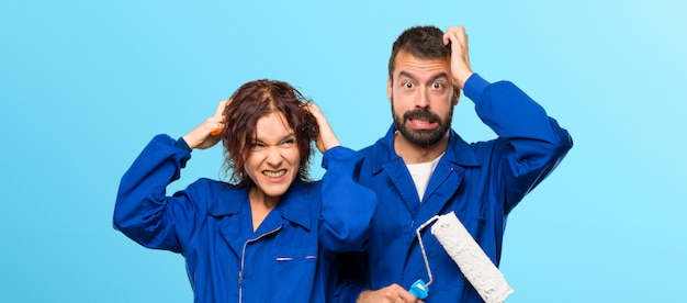 Painters takes hands on head because has migraine on colorful background Premium Photo
