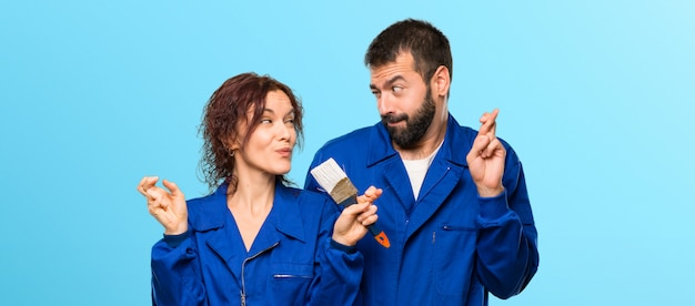 Painters with fingers crossing and wishing the best on colorful background Premium Photo